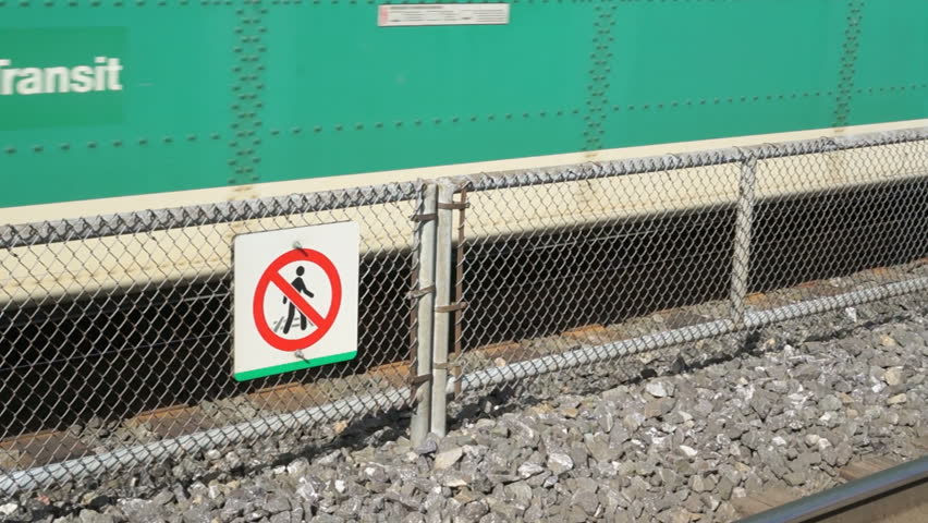No crossing railroad tracks warning sign with train. Sign to warn people not to cross the train tracks, with a train moving behind it. A sign warning for danger, GO train moving in the background. - HD stock video clip