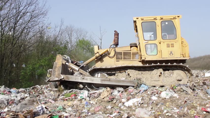 9/35 SRBIJA,KRUSEVAC,2014. Bulldozer (tractor) pushes a pile of trash at landfill. Vehicle flattening garbage to waste.Bulldozer moves non biodegradable garbage at the dump.Truck working on dump.30fps - HD stock video clip
