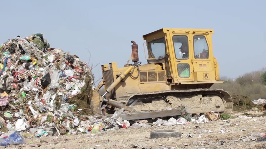 5/35 SRBIJA,KRUSEVAC,2014. Bulldozer (tractor) pushes a pile of trash at landfill. Vehicle flattening garbage to waste. Bulldozer moves non biodegradable garbage at the dump. Dogs searching food.25fps - HD stock video clip