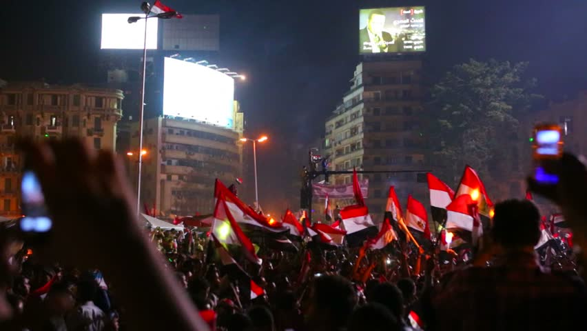 View from the ground as protestors chant, wave flags, and take cell phone pictures at a large nighttime rally in Tahrir Square in Cairo, Egypt.