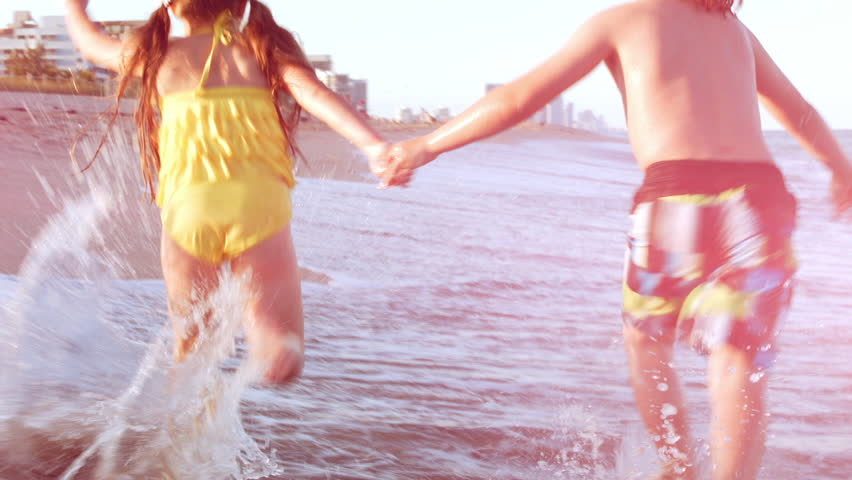 Little Kids Hold Hands And Run As Fast As They Can (Away From Camera) Down Beach, Beautiful Lens Flare