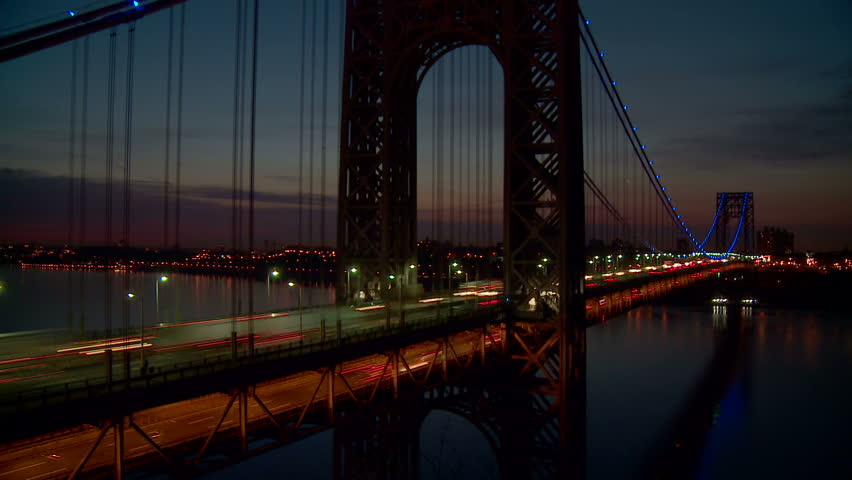 Timelapse view of morning rush hour traffic on the George Washington Bridge crossing the Hudson River between New Jersey and New York before sunrise. Blue bridge lights in support of Autism Awareness. - HD stock footage clip