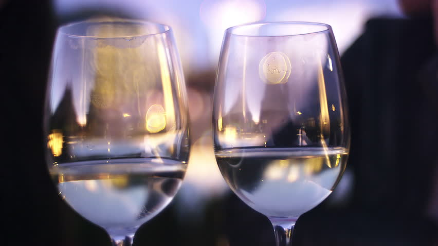 Close up of two wine glasses being toasted at sunset - 4K stock video clip