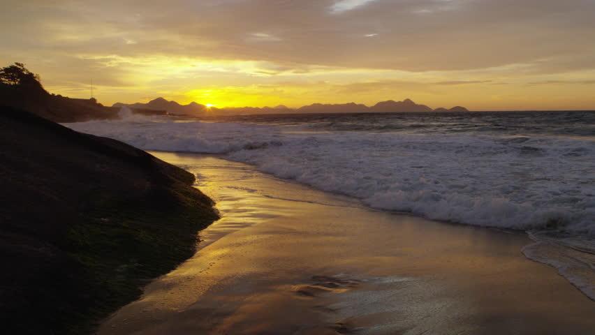 Slow-mo, static shot of killer waves hitting the beach and cliffs at Praia do