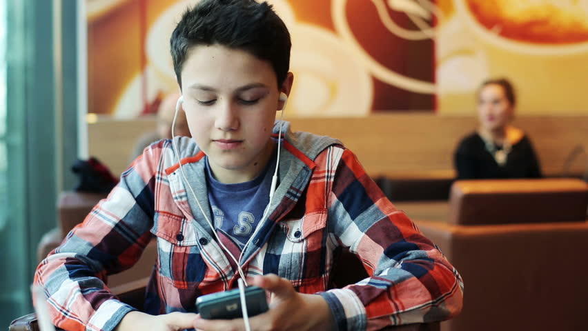 Young teenager with earphones listening to the music in cafe