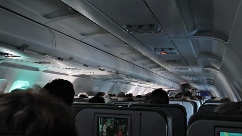 ORLANDO, FLORIDA - JAN 2014: International flight crowded passenger compartment. Turbulence as passengers are bounced around flight cabin. Commercial airline over landscape, ocean, and terrain.   Shutterstock HD Video #6128177