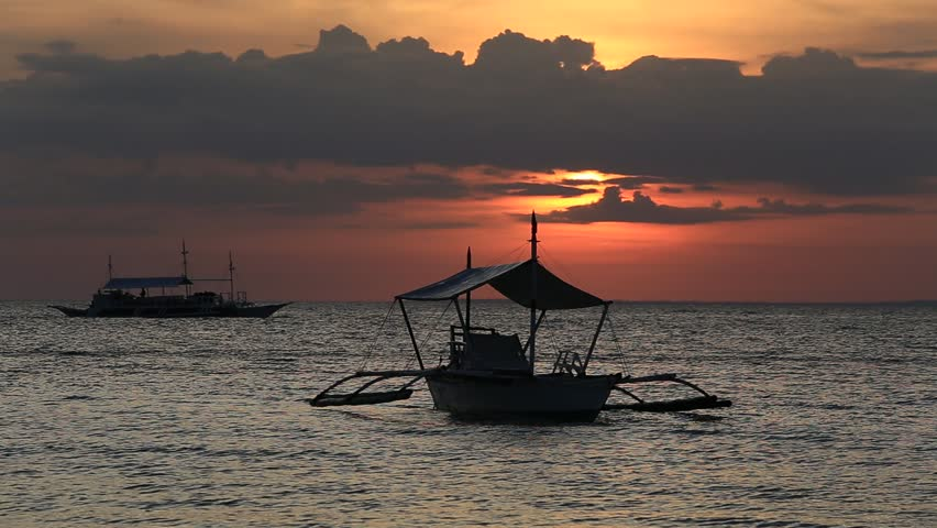 MALAPASCUA, PHILIPPINES - MARCH 07, 2014 : Philippine tourist boat sails on the sea at sunset. Philippines is one of the top tourist destinations in the world.
