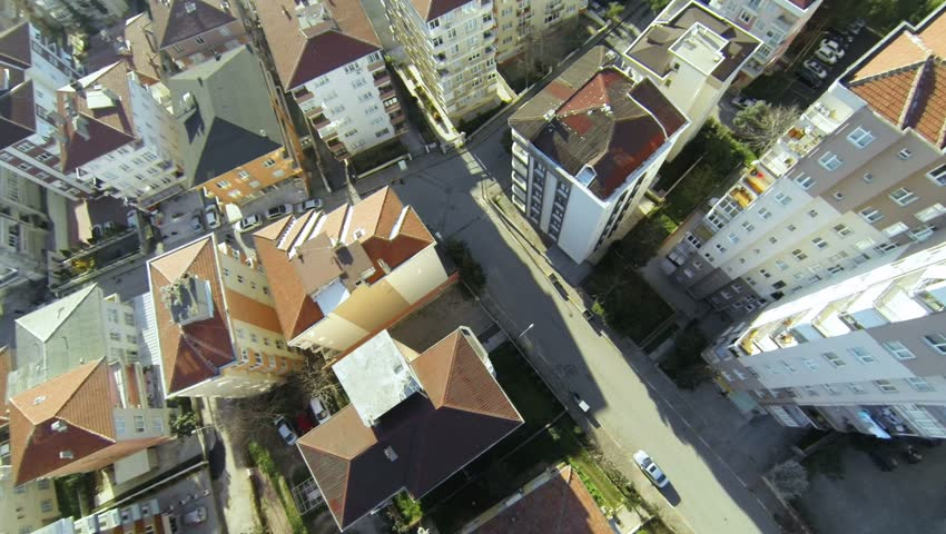 Top down city blocks. Flying over streets and houses along suburban architecture in Istanbul. Aerial video of rooftops from flying camera.