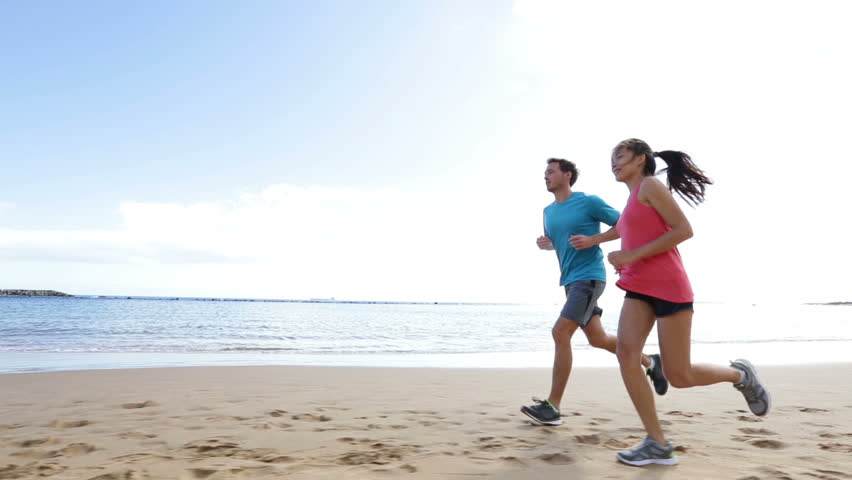 Runners running on beach. Jogging couple training on beach in full body length living healthy active lifestyle. Asian runner woman and fit male fitness athlete on run.