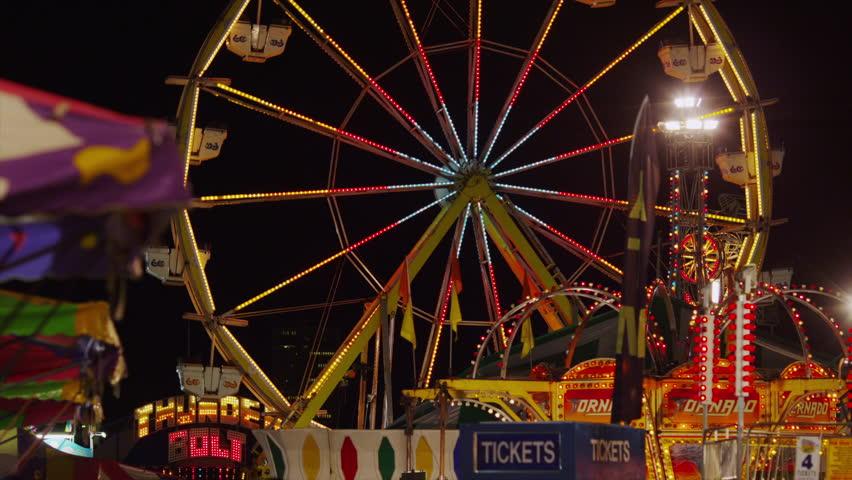 SALT LAKE CITY, UTAH, USA - July 18, 2013 - Slow motion wide shot of Ferris Wheel at amusement park at night  - HD stock video clip