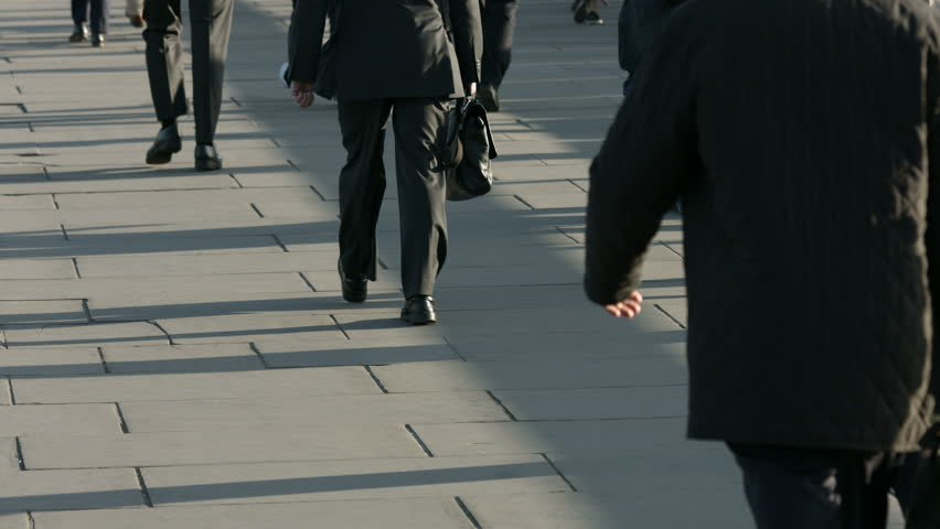 Large crowd of commuters and pedestrians walk across London Bridge to the City of London on a sunny morning 4K. Clip 09