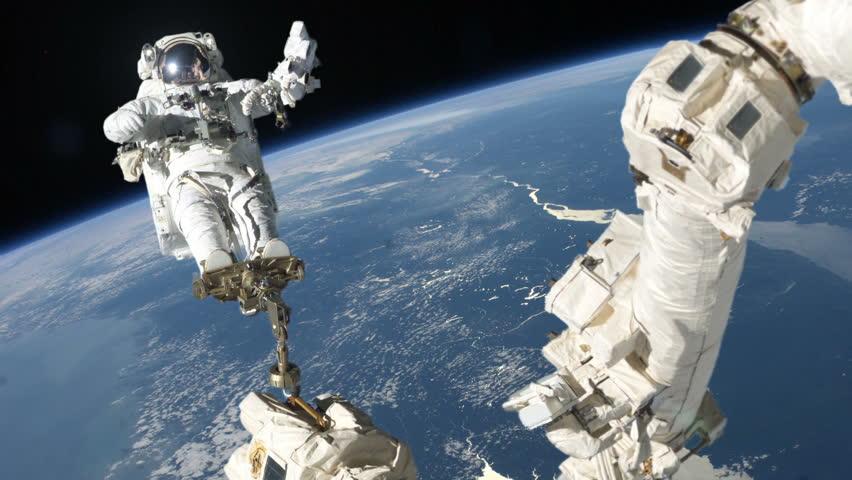 Astronaut repairing satellite on crane