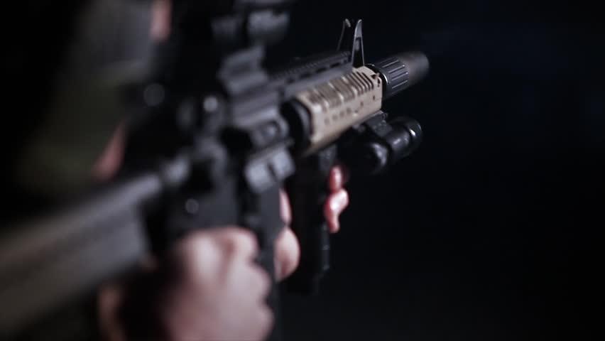 Close up of man firing artillery rifle, shallow depth of field