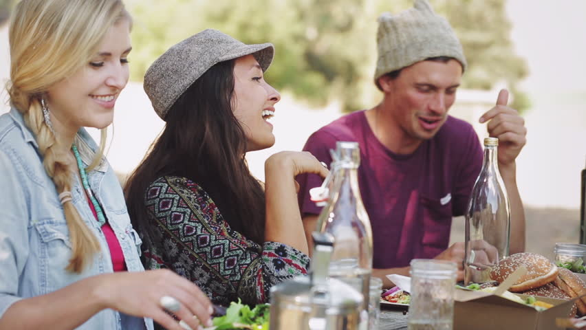 Side view of a group of friends on a park picnic table eating and talking