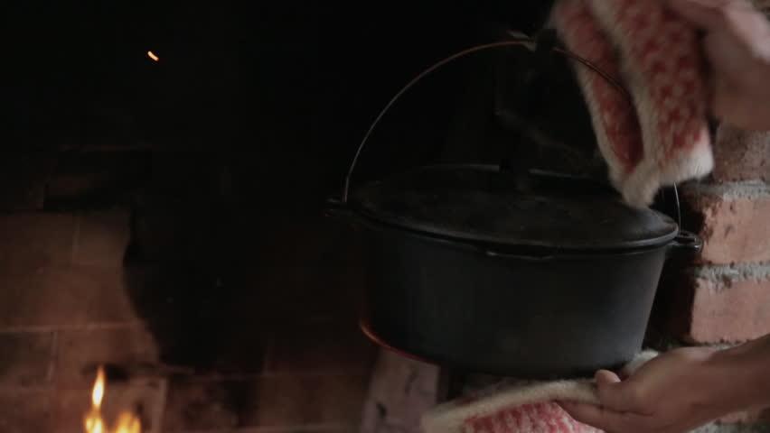 Man placing a metal pot on a fireplace - HD stock video clip