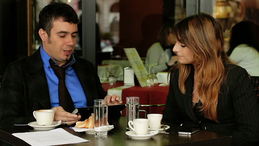 Business meeting. Businesswoman and businessman in cafe, talking. - HD stock footage clip