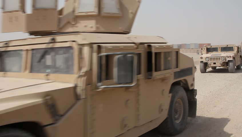 four humvees pass moving camera on airbase in middle east
