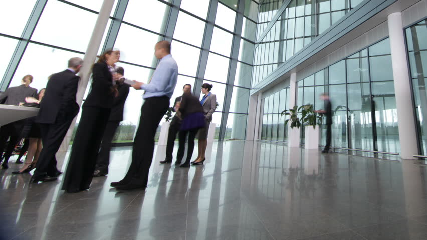 Time lapse of diverse business group in a large modern corporate building - HD stock footage clip