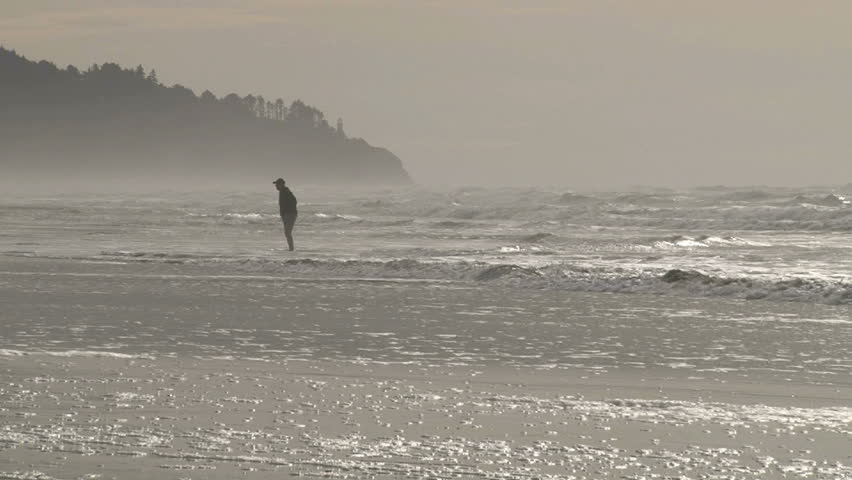 Man stands in Pacific ocean as tide comes in and two friends join.
