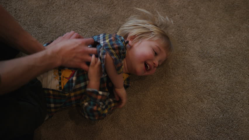A young boy is tickled while rolling around on a carpeted floor.