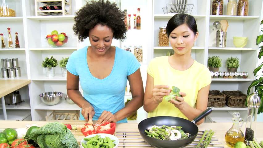 Healthy Asian Chinese African American Females Fresh Organic Produce - Asian Chinese African American girlfriends modern home kitchen preparing fresh organic stir fry vegetables healthy lunch