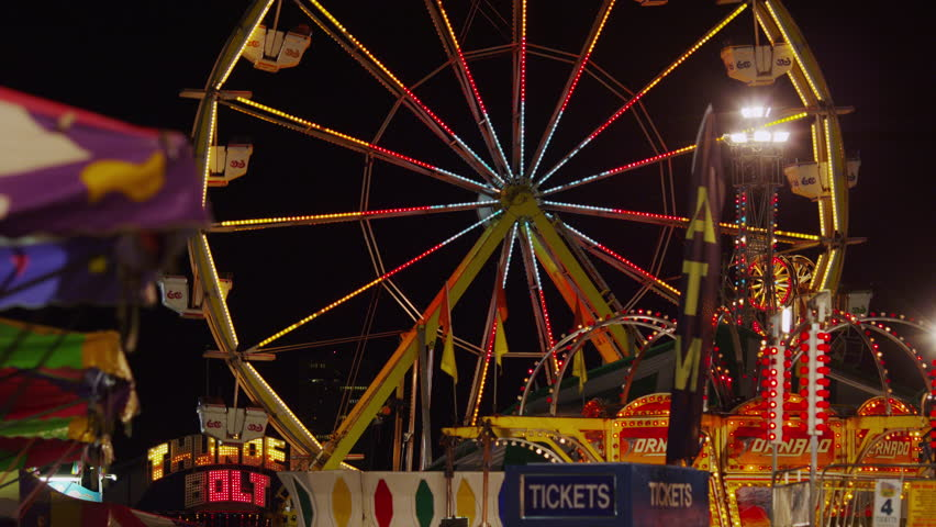 SALT LAKE CITY, USA - July 18, 2013 - Slow motion wide shot of Ferris Wheel at amusement park at night  - 4K stock video clip