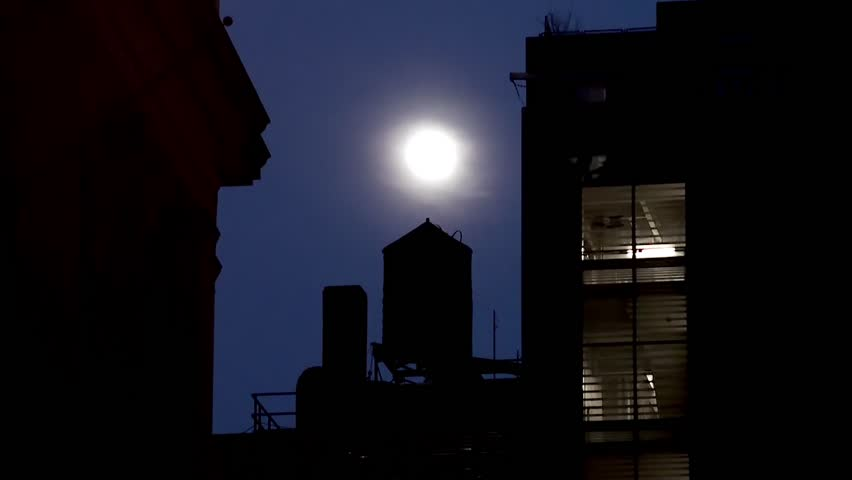 Water tower at the roof of the NYC building at night.