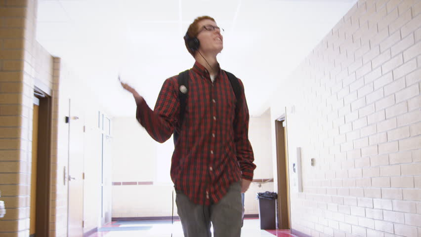 SLO MO Medium Shot Male student wearing headphone dancing in school corridor
