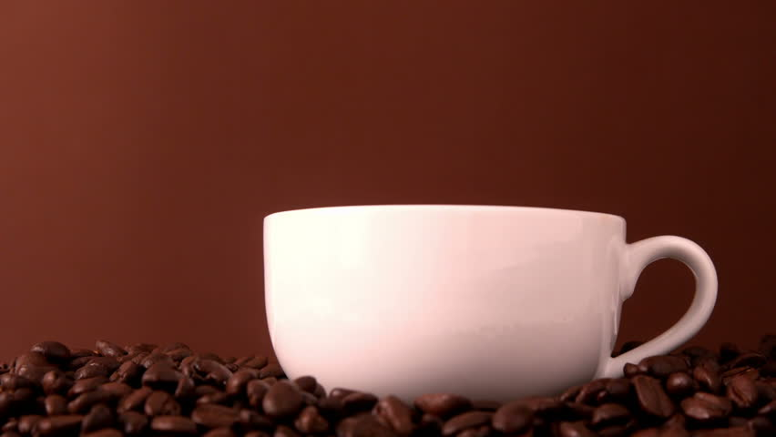 Hot coffee pouring into white cup in slow motion
