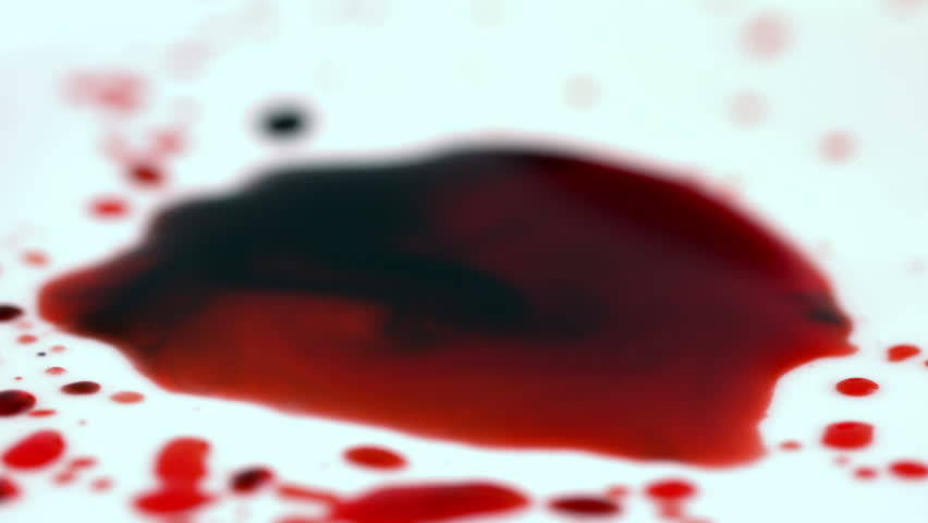 Blood dropping onto white surface in slow motion