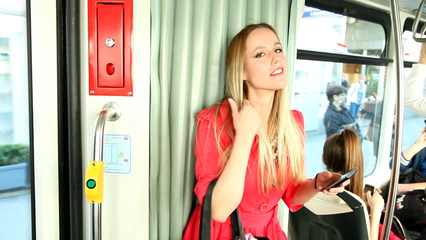 Beautiful blond young woman standing in tram, talking on the phone