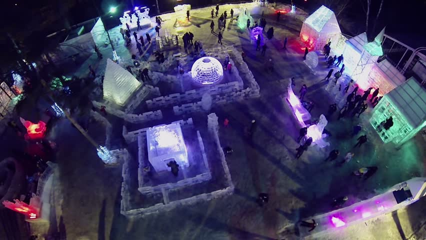 Many people walk around Ice Town in Sokolniki Park at winter night. Aerial view