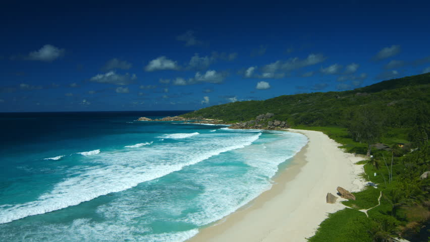 4K tropical island with sandy beach and waves on sunny day