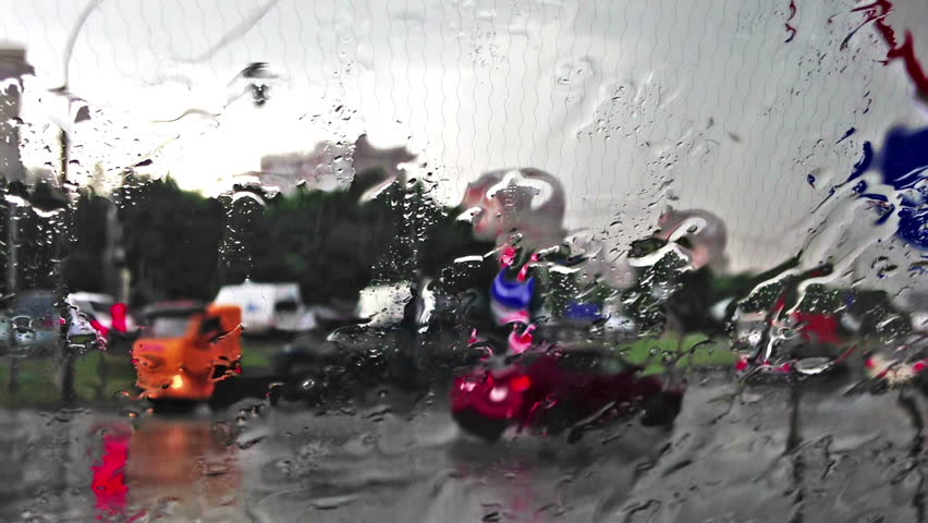 Rain in the city. Shot through the windscreen with heating threads. Focus on the water droplets. - HD stock footage clip
