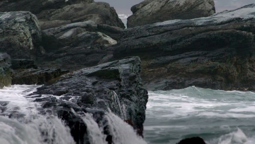 Waves crash against the rocky coast, in slow motion