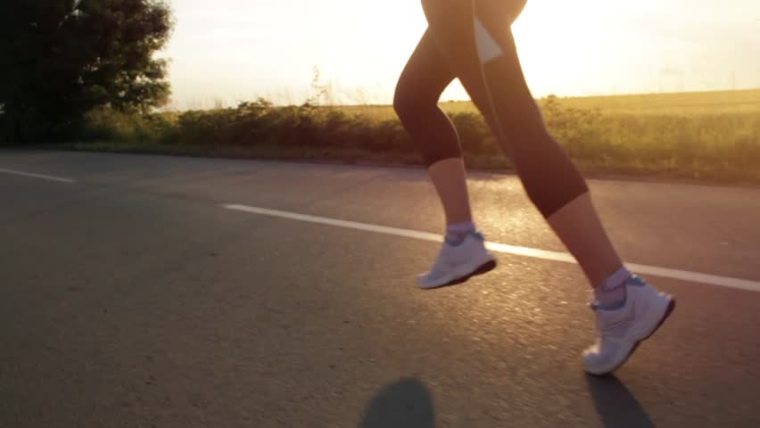 Female Legs Feet Running on Country Road Exercising Concept