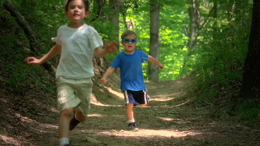 Two boys running in the forest together laughing and playing and jumping in slow motion.