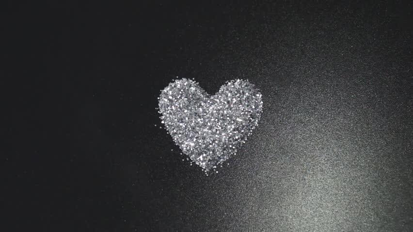 silver glitter arrange to heart shape on black background