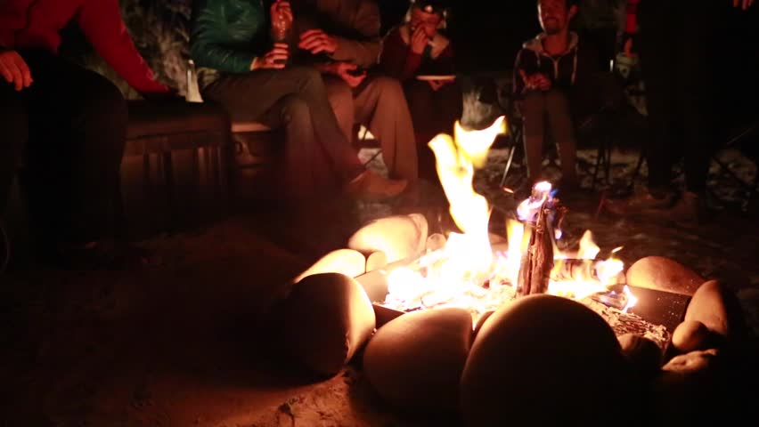 Family sitting around campfire while camping - HD stock video clip
