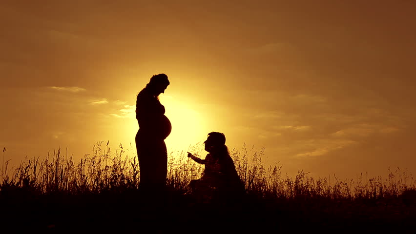 Beautiful shot of happy family: pregnant mother, father and little daughter at sunset. Silhouettes. | Shutterstock HD Video #6518084