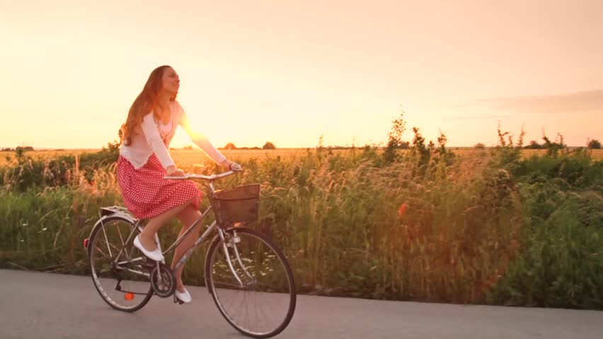 Free Happy Woman Riding Bicycle at Sunset Summer Field