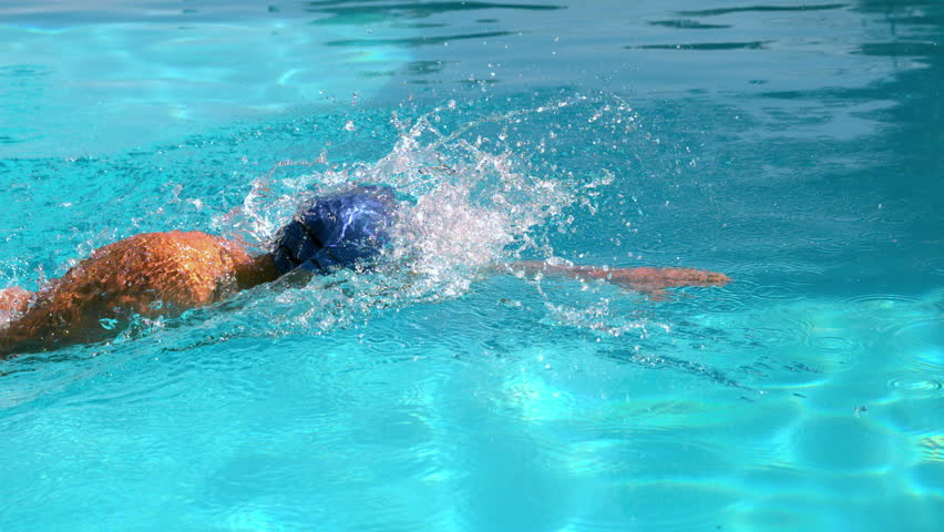 Fit swimmer doing the front stroke in the swimming pool in slow motion - HD stock video clip