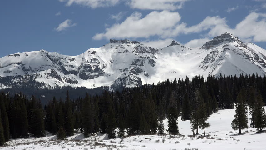 Rocky Mountains snow peaks clouds fast time lapse. Beautiful mountains near Telluride, Colorado. Spring time with snow and forest in nature. Clouds drifting along top of Rocky Mountain peaks. | Shutterstock HD Video #6569996