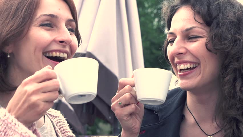 Beautiful women drinking coffee in cafe and talking. High speed camera shot 1080p. Slow motion video footage. High speed camera shot