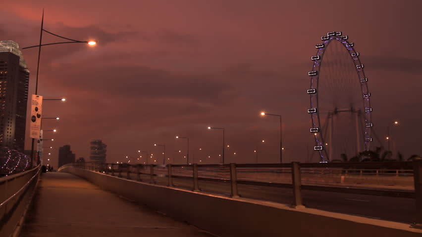 Singapore_21 May, 2014: Time lapse of Singapore Flyer and traffic at Marina Bay in Singapore at sunset - HD stock footage clip