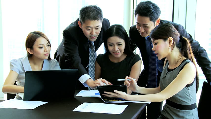 Asian Chinese successful business team conference together modern city boardroom discussing latest financial results seen laptop computer touch screen tablet technology