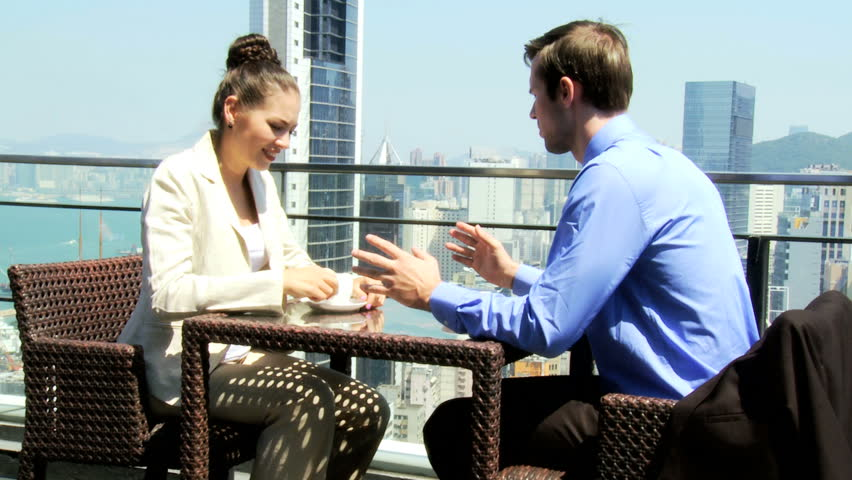 Young male female Caucasian business people sitting rooftop luxury restaurant downtown drinking coffee
