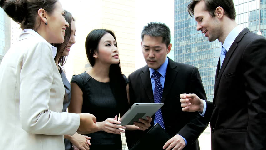 Smart multi ethnic corporate business team wireless mini tablet hot spot outdoors excited good news modern downtown city skyscrapers background