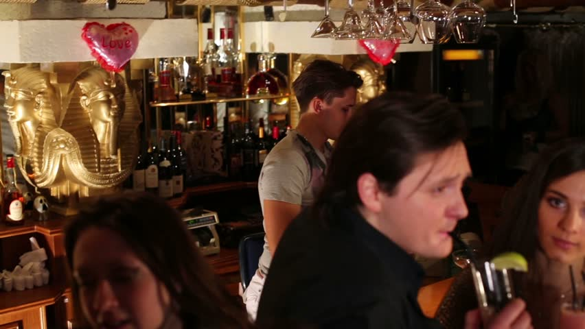 Sixteen men and women relax with cocktails at party in bar of night club - HD stock video clip