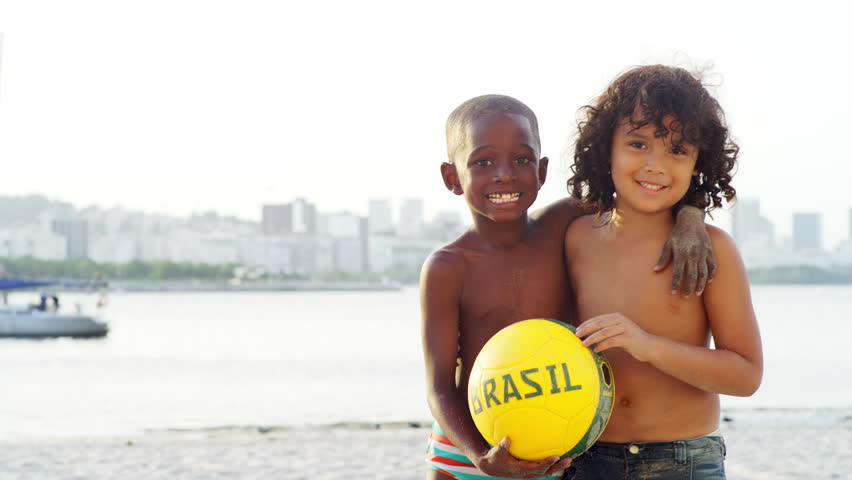 Kids pose and smile with a soccer ball on a beach
